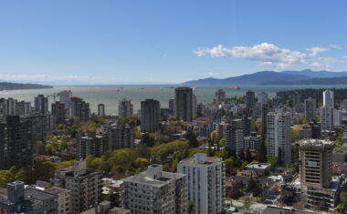 View of downtown Vancouver from the top of the Blue Horizon Hotel in Vancouver. You can see the mountains in the background as well as the ocean.