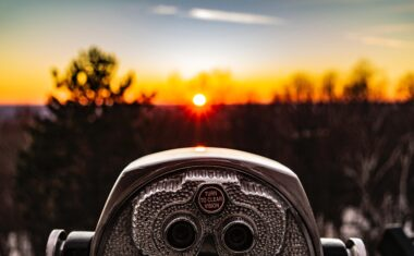 Photo of a stand binocular pointed at a sunset