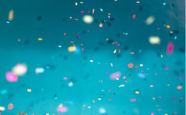 Confetti paper falling in front of a blue backdrop