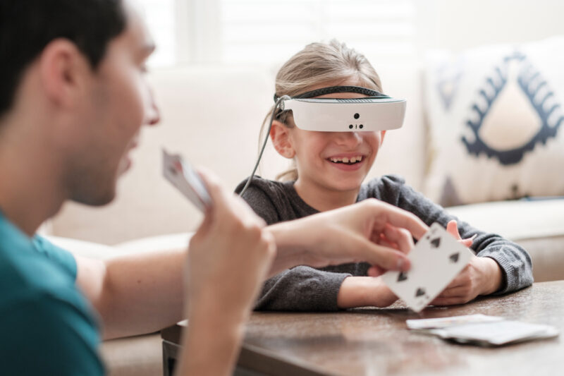 Young girl wearing eSight glasses holding cards in her hand playing with a man