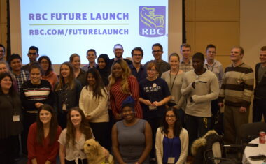 A group of Young Leader attendees standing in front of a projector with the RBC Future Launch Logo on it