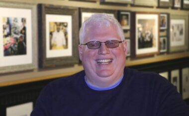 Dave Brown standing wearing transitional sunglasses smiling at the camera