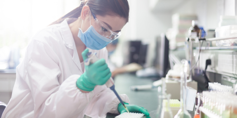 Female Scientist working in a lab with a mask and goggles on