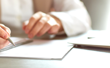 person sitting at desk signing documents