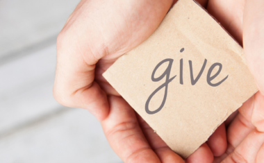 hands holding a block with the word give on it