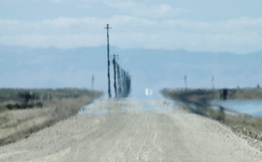 image of a long blurry road blending into a blue sky horizon
