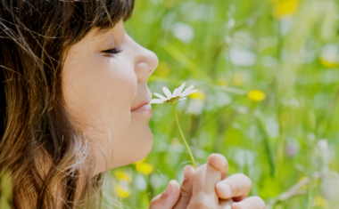 close up of girl smelling a flower in green field