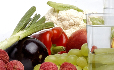 image of a variety of fruits and vegetables on a table with a jug and glass of water