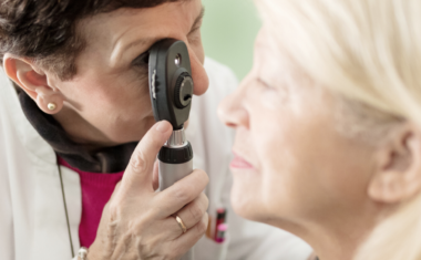 image of an eye doctor examining the eye of a senior patient