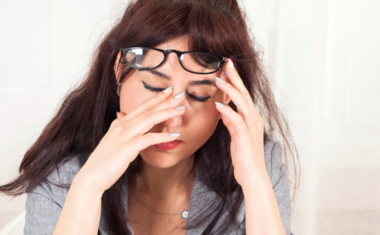 image of young female at desk rubbing her eyes