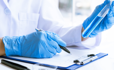 image is of a medical researcher wearing medical gloves, holding a vile and recording information onto a clipboard inside a laboratory.